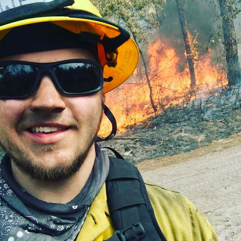 man in front of controlled fire in mike roess gold head state park while he smiles