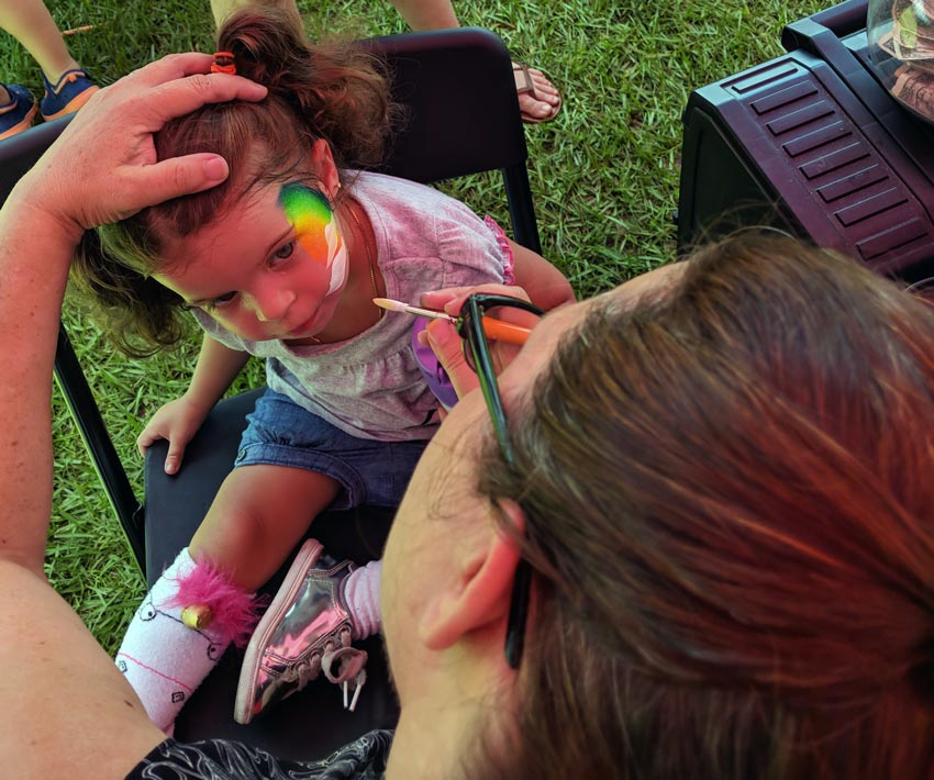 little girl gets her face painted at watermelon festival