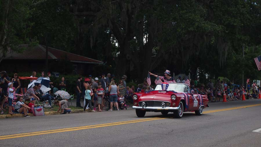 Red classic car is in 4th of july parade in Keystone Heights.