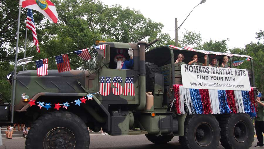 Big army truck with Uncle Sam driving it and martial art students in back of truck are in keystone heights 4th of july parade.