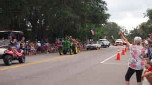 Golf Cart and tractor in parade, keystone heights spectators waving at them