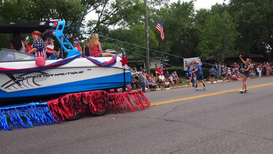 Skateboarders being pulled by a decorated independence day boat float, mimicking as if they were water skiers.