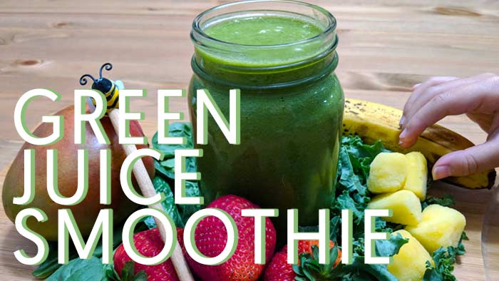 Green Juice surrounded by kale, spinanch, banana, pineapple, honey, with a hand coming out of screen reaching for pineapple