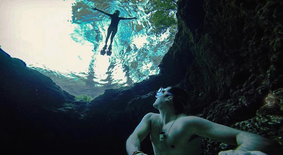 underwater swimmer in cave looks up to another swimmer in high springs florida